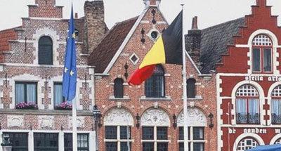 Bandera de Bélgica y fachada de una casa en Flandes