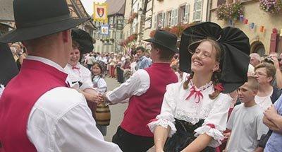 Hombre y mujer bailando en traje tradicional de Alsacia