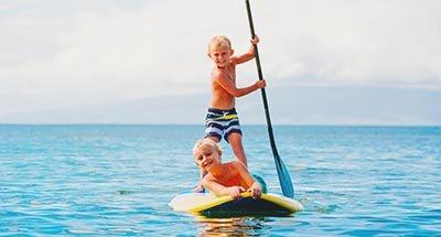 Dos chicos haciendo paddle-board