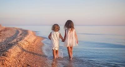 Dos niños caminando en la playa