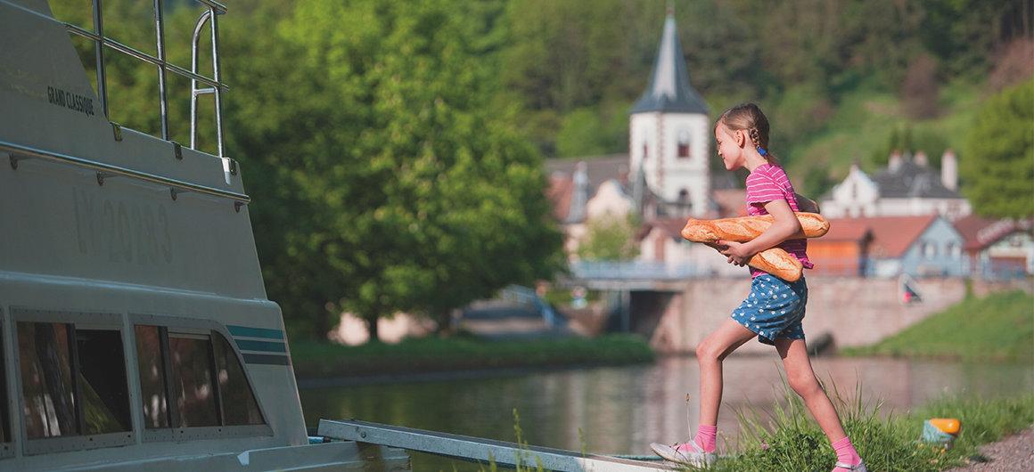 Chica llevando el pan a bordo de un barco